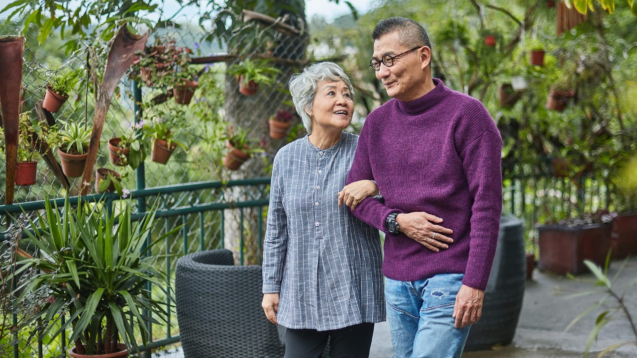 "An old couple is walking in the garden; image used for ""how to stay financially healthy"" article."