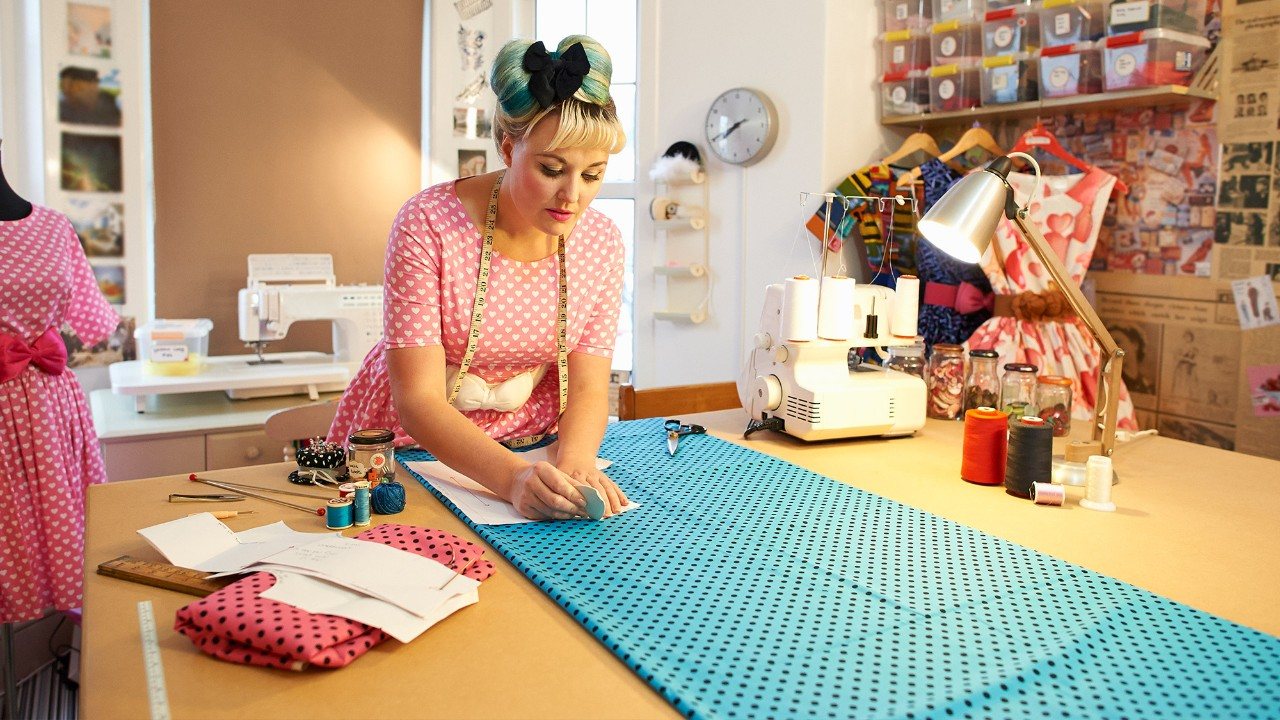 "A woman is sewing clothes; image used for ""getting financially fit"" article."