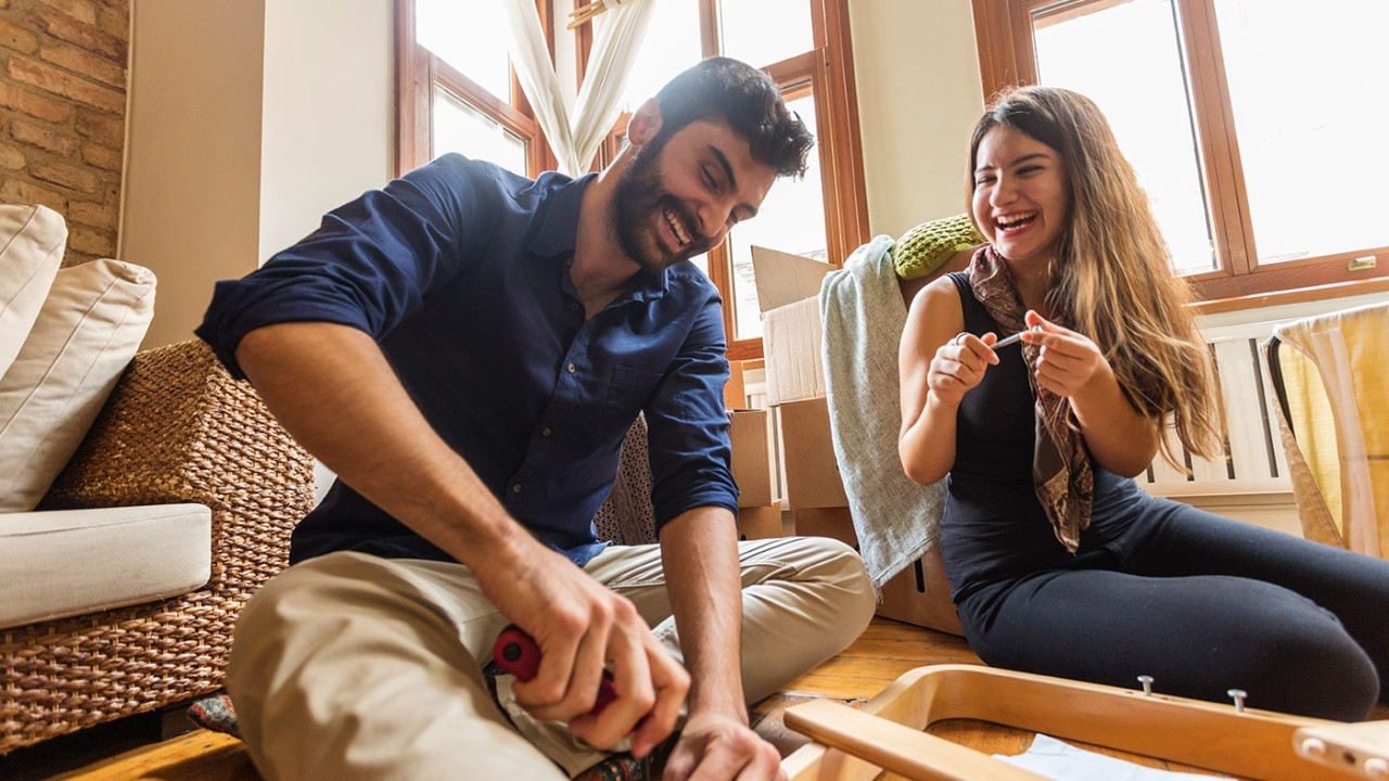 a couple assembling furniture together happily; image used for HSBC LK Advance Preferential rates on borrowing page.