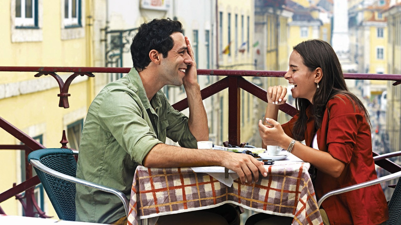 a young couple chatting happily in a cafe's balcony seats; image used for HSBC LK Preferential rates and rewards page