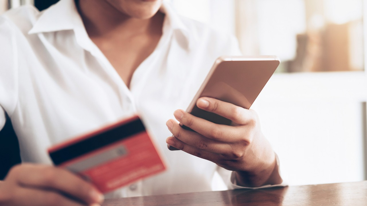 a woman holding a card and a mobile phone; image used for HSBC Sri Lanka credit card useful links page.
