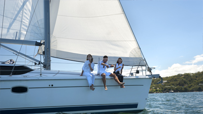 Three people on sailing boat happily; image used for HSBC Sri Lanka Homepage
