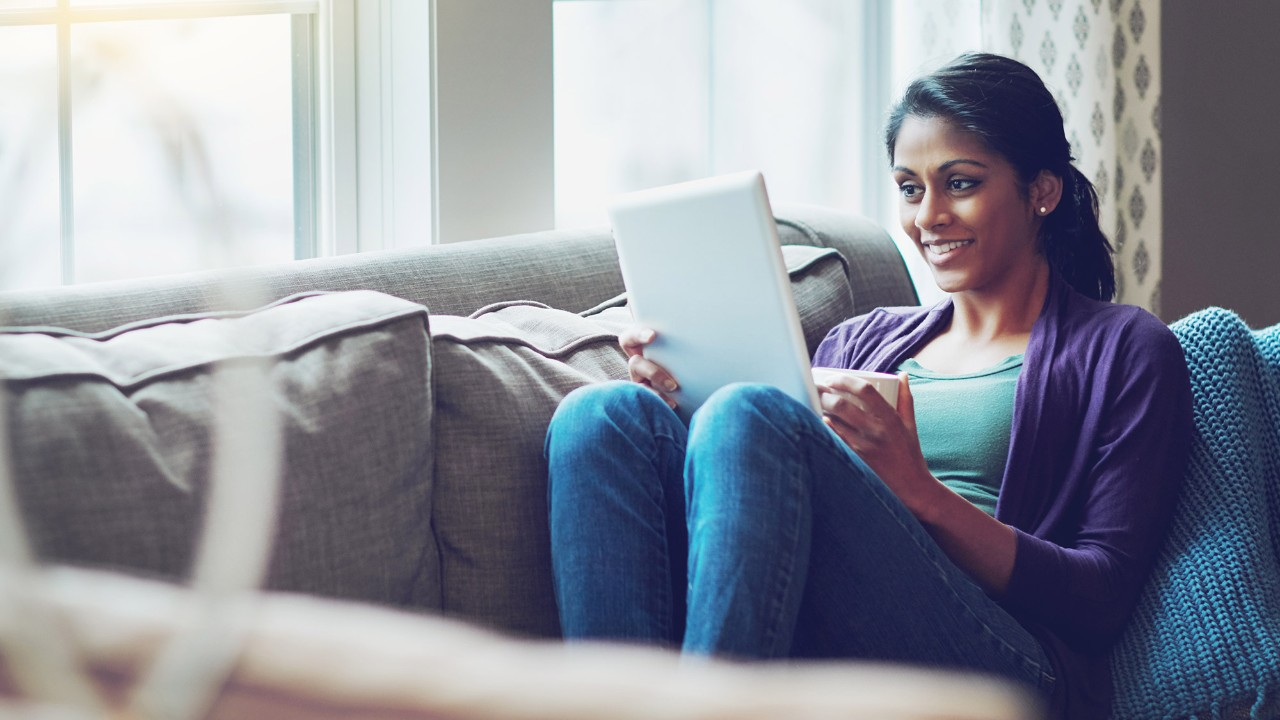 Happy woman using tablet on a couch; image used for HSBC Sri Lanka Ways to Bank
