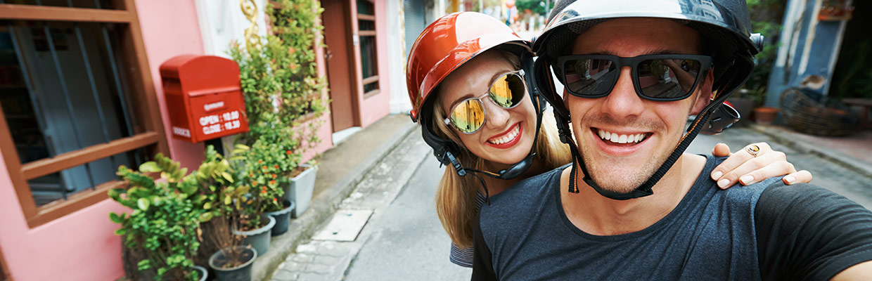 Happy couple on bicycle with helmets on; image used for HSBC Sri Lanka Visa Signature Credit Cards