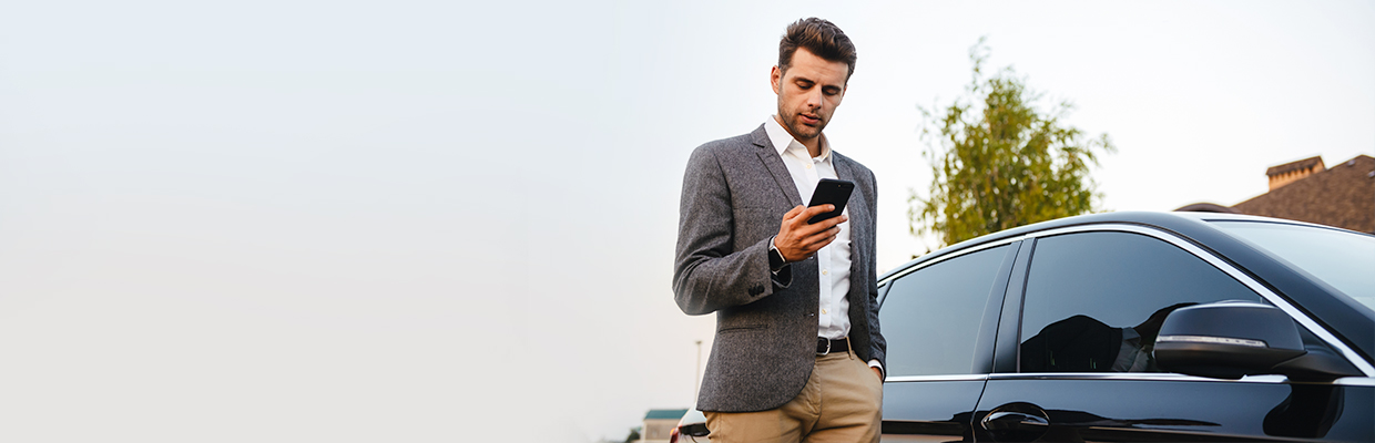 a man checking his mobile phone beside a car; image used for HSBC LK Advance Bank in your pocket page.