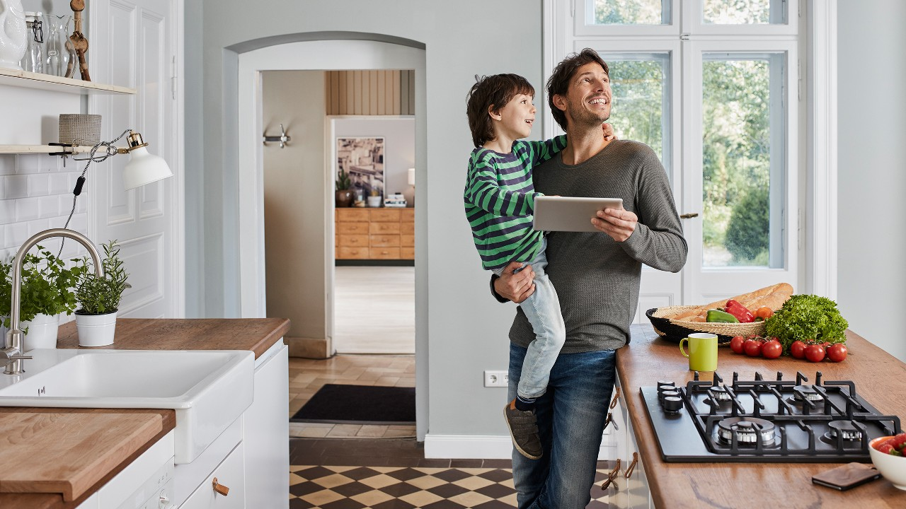 A father happily holding his son with a tablet in the other hand, looking around in a kitchen;  image used for HSBC Sri Lanka credit card household offer page