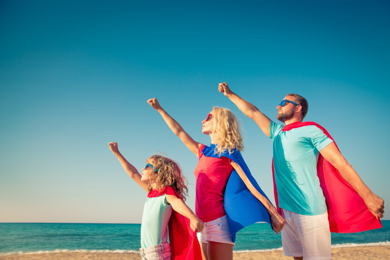 family of superheroes on the beach