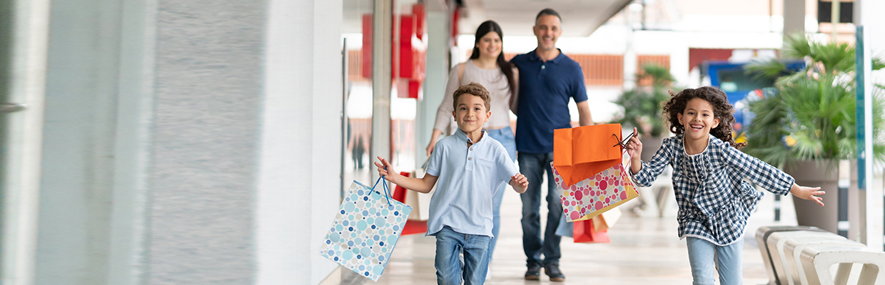 A boy and a girl running happily with shopping bags with their parents walking behind them; image used for HSBC Sri Lanka credit card offer page