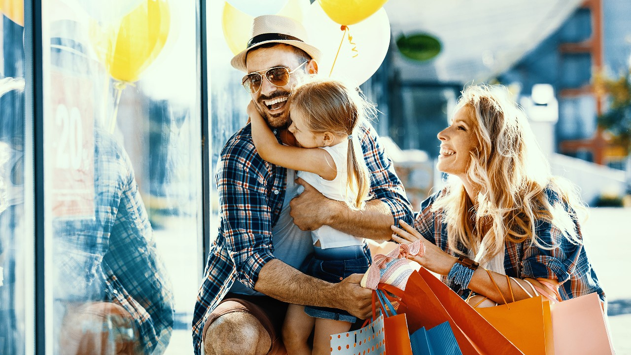 Parents holding their girl happily and with shopping bags and ballons outside a shop window; image used for HSBC LK credit cards rewards page
