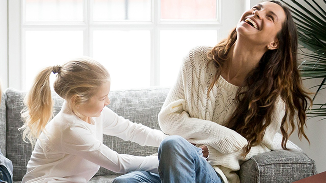 A mother is playing with her daughter happily on the sofa; image used for HSBC Premier personal lending Landing Page