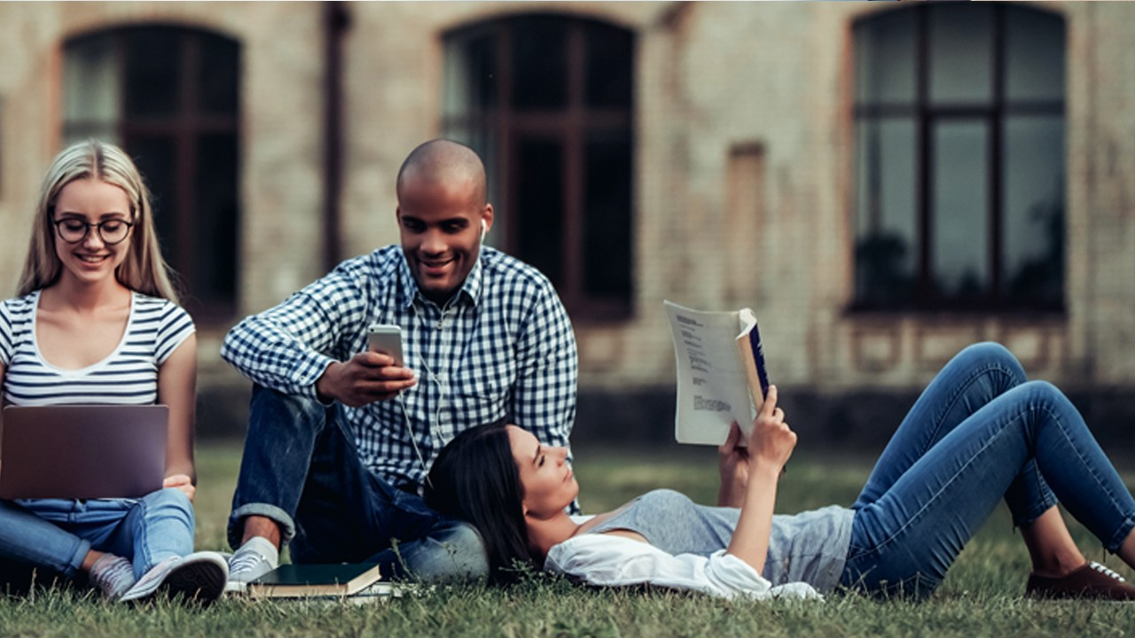 Three students are reading and talking happily on university's grassland; image used for HSBC Premier Next Generation Landing Page