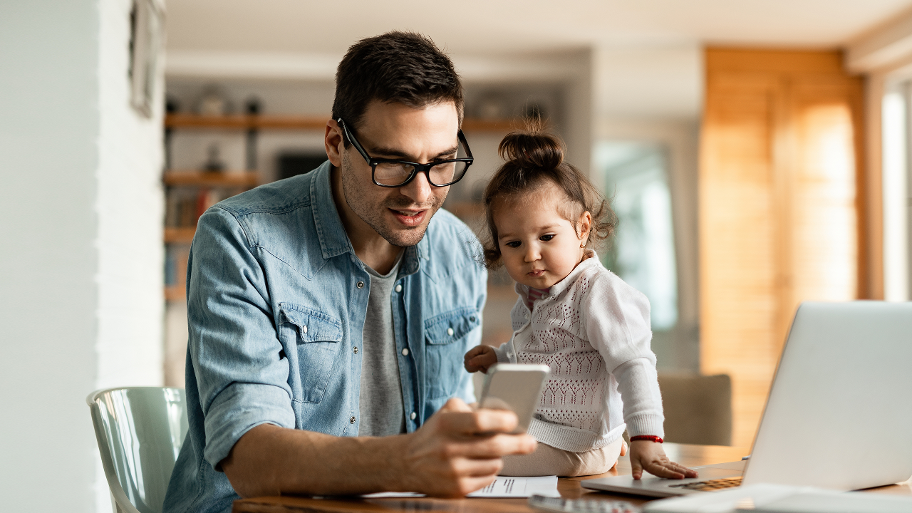 A man together with his little girl looking and his mobile phone; image used for HSBC LK mobile banking page.