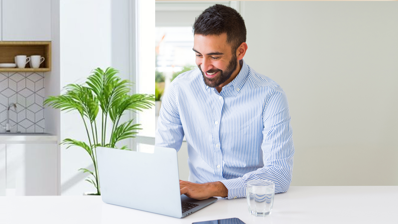 A man happily using laptop at home; image used for HSBC LK online banking page.